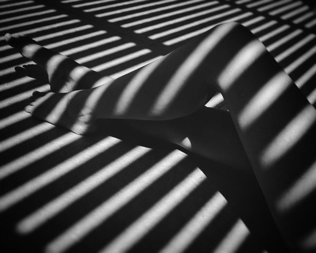 Low section of woman sitting in shadow of blinds