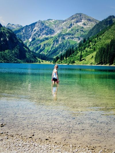 Young woman standing in lake by mountains