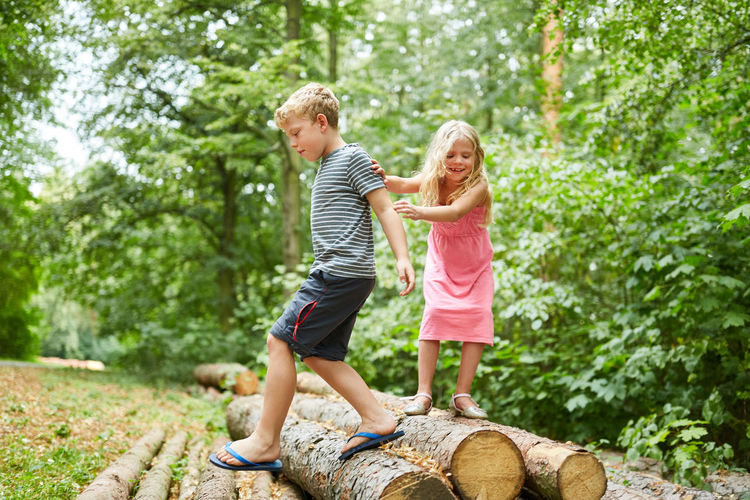 Male and female sibling playing over log against forest