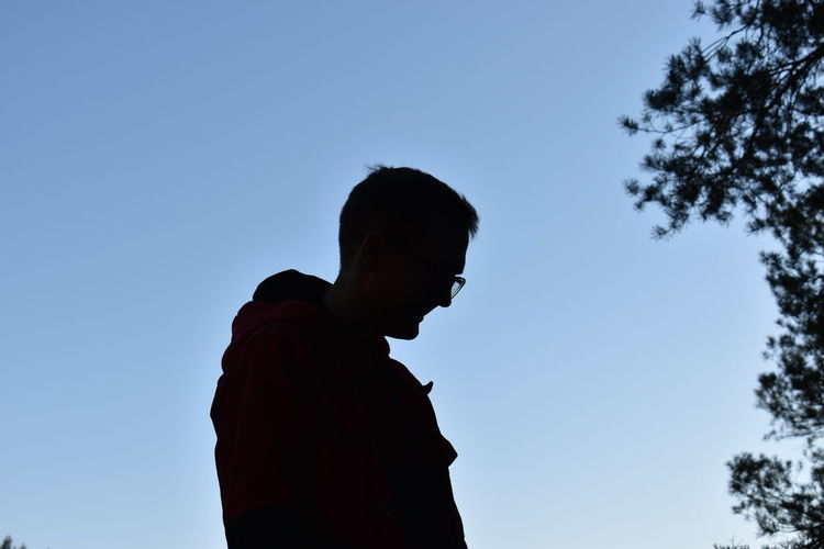 Low angle view of silhouette man standing against clear blue sky