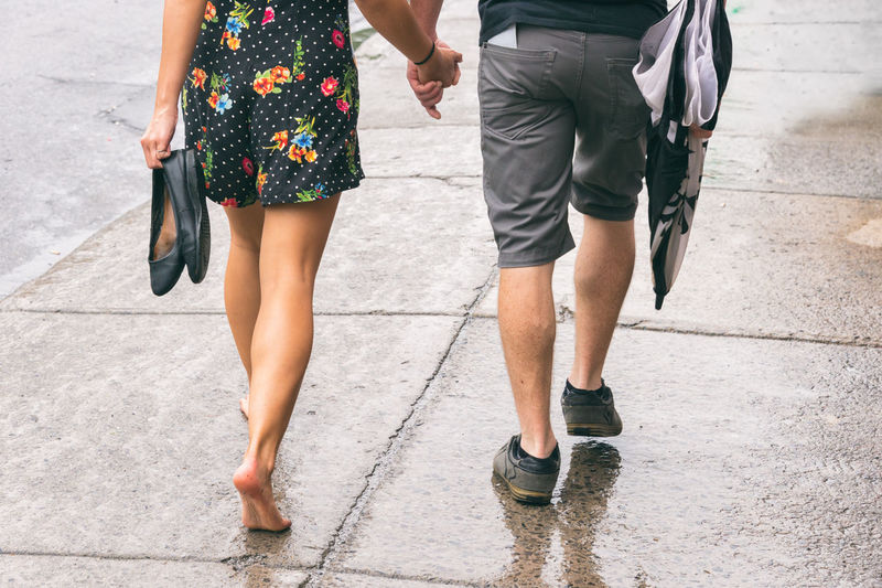 Low section of couple walking on street