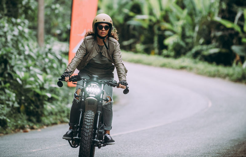 Full length of woman riding motorcycle on road