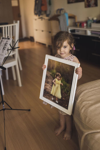 Portrait of smiling girl holding camera at home