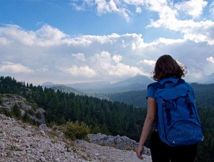 Rear view of young woman with backpack walking on mountain against cloudy sky