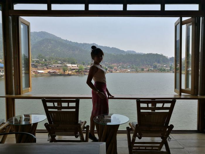 Only Women Full Length Indoors  Domestic Life Women Cityscape Balcony Tranquility One Person Lake View Terrace