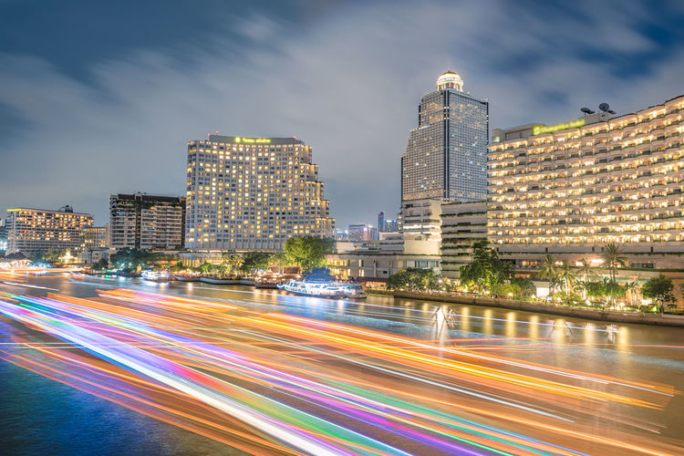Cityscape chao Phraya river at night in Bangkok ,Thailand. Architecture Blurred Motion Building Exterior Built Structure Business; Modern; White; Water; Architecture; Building City City Life Cityscape Illuminated Light Trail Long Exposure Modern Motion Night No People Outdoors River; Phraya; Chao; Bangkok; Thailand; Road Sky Skyscraper Speed View; Blue; City; Sky; Travel; Boat; Cruise; Night; Cityscape; Twilight; Water