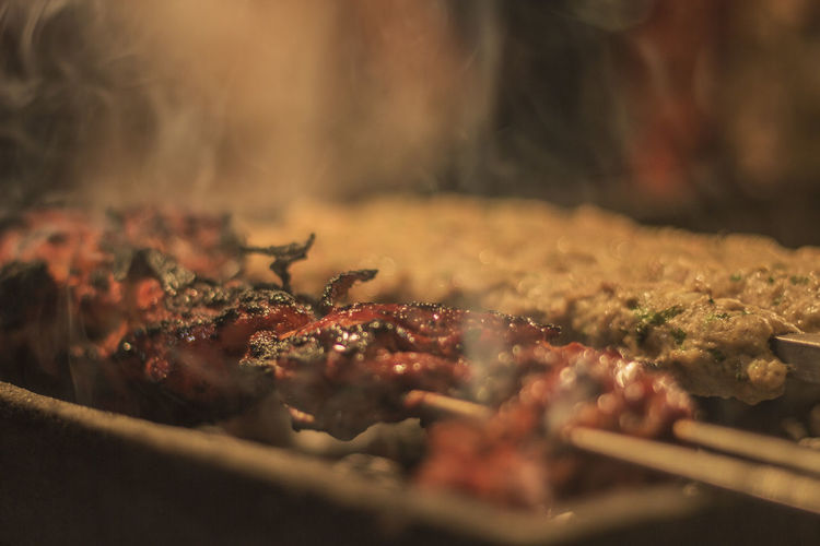 Close-up of roasting chicken in skewers at market stall