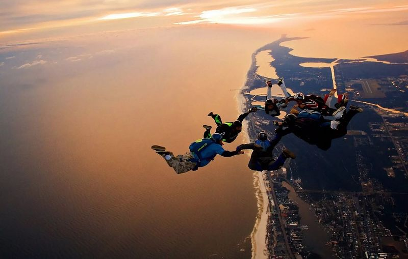 People Skydiving Over Landscape During Sunset