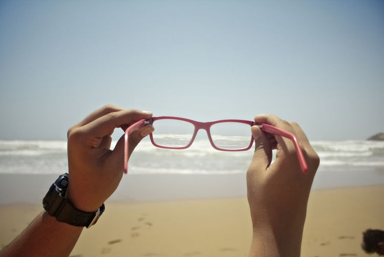 Cropped hand holding eyeglasses on beach against clear sky
