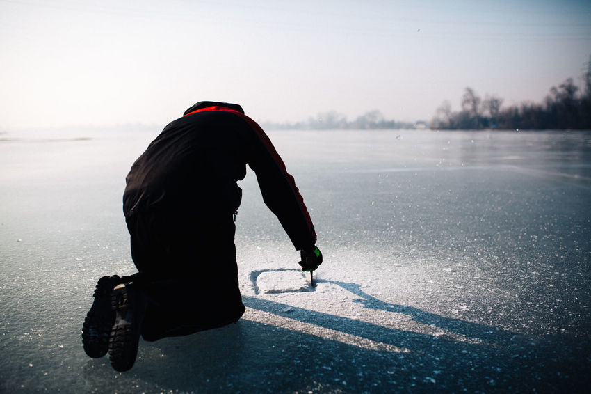 On ice Adult Axe Belowzero Cold Temperature Determination Fishing Freezing Ice Icefishing Leak Nature One Man Only One Person Onice Outdoor Pursuit Outdoors Rear View Recreational Pursuit Shadows & Lights Snow TeamCanon Warm Clothing Winter Winter Sport