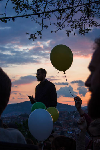 Silhouette people on balloons against sky during sunset