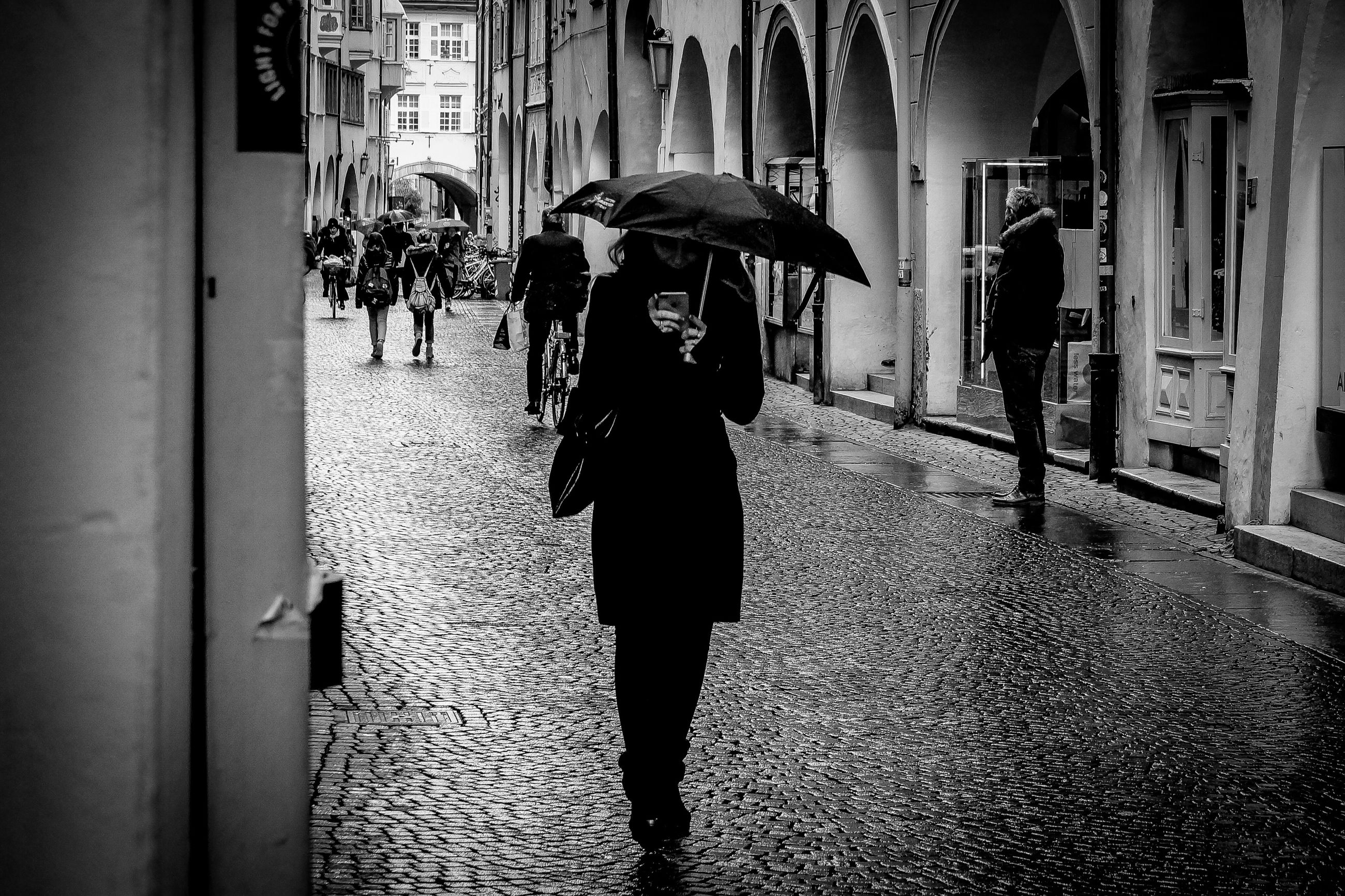 real people, architecture, built structure, building exterior, one person, lifestyles, protection, women, city, leisure activity, adult, standing, umbrella, wet, street, walking, incidental people, security, clothing, rain, rainy season, beautiful woman