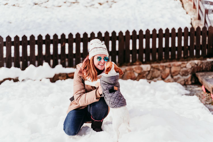 Portrait of young woman crouching on snow with dog
