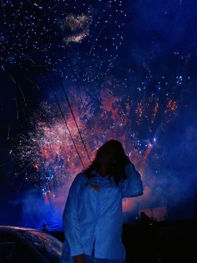 Woman standing by car against fireworks in sky at night