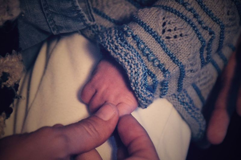 Cropped hand of woman holding baby hand