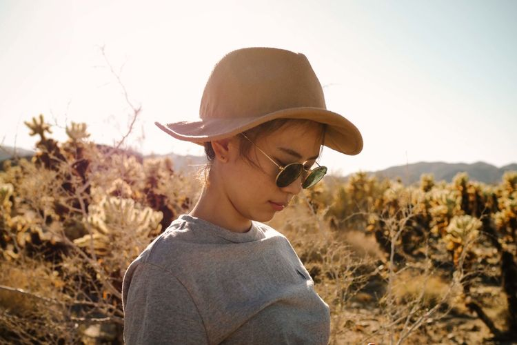 Close-up of girl wearing hat against sky