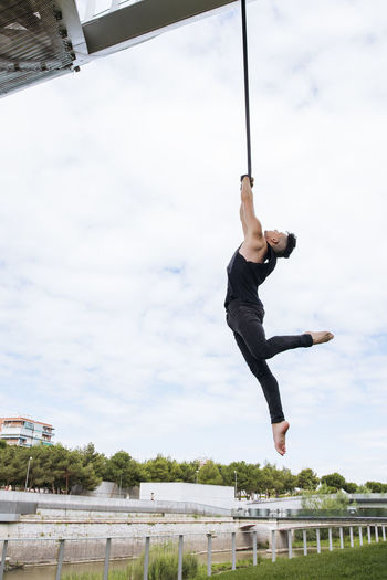 Low angle view of man jumping hanging against sky
