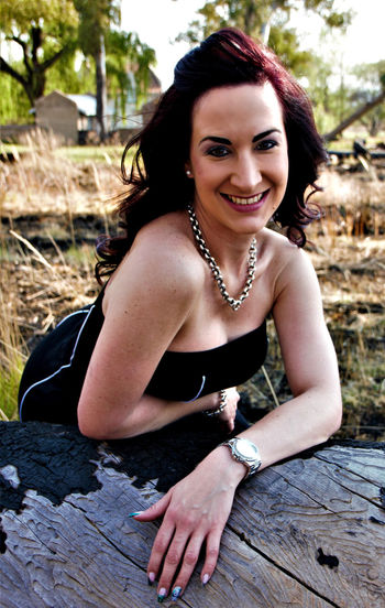 Portrait of smiling woman leaning on wooden bench