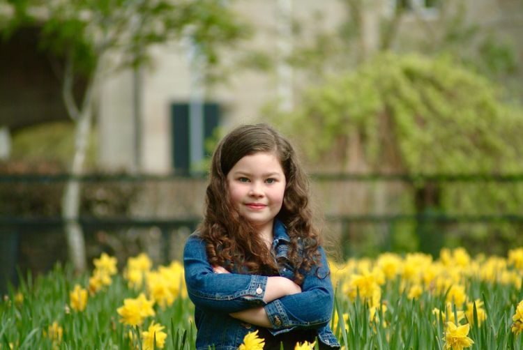 Portrait Of Girl Standing With Arms Crossed Amidst Daffodils At Park