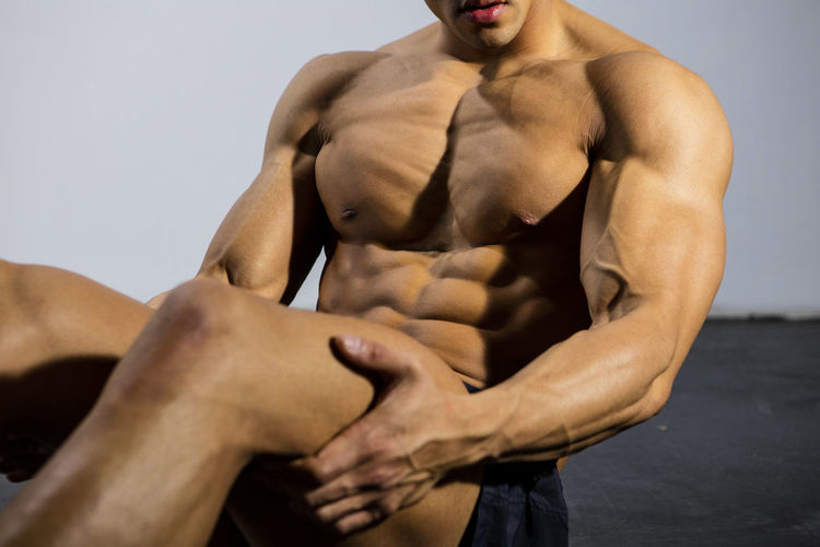 The torso of a fitness model sitting down. Body shot only no face. Muscles flexing. Adult Asian  Athlete Body & Fitness Human Body Man Nam Vo Shirtless Sitting Sportsman Abs Fitness Model Flexing Grey Wall Handsome Hunk Male Muscle Muscular Build No Face One Person Pectoral Muscles Strong Studio Shot Torso