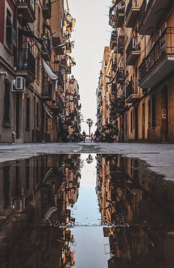 Built Structure Architecture Reflection Water Building Exterior City Sky Building Residential District Puddle Alley Outdoors No People Street Symmetry