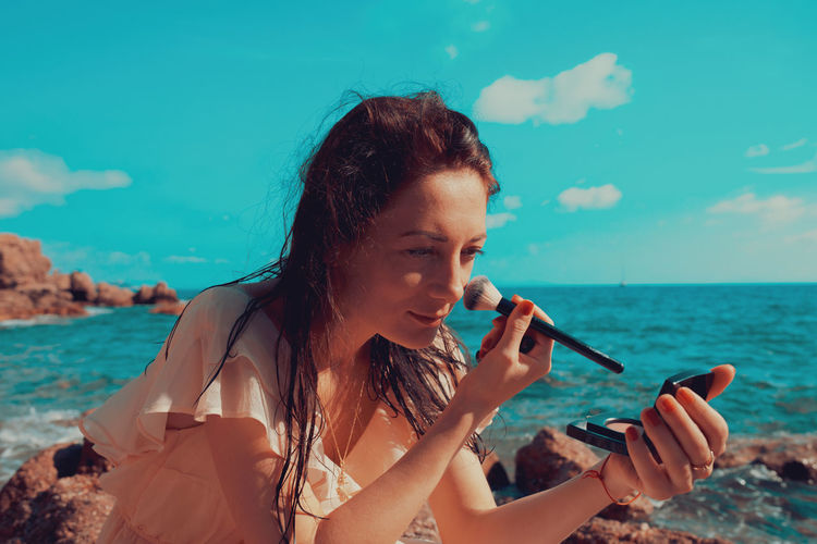 Woman applying make-up while sitting at beach against blue sky