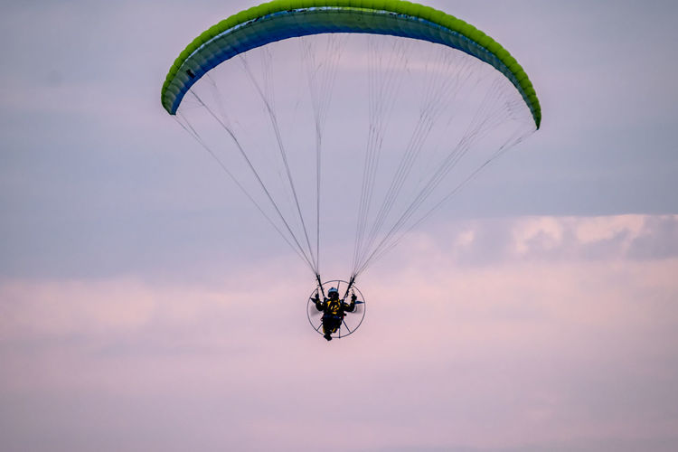 Man paragliding against sky during sunset