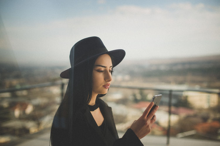 Beautiful young woman seen through glass window using phone standing against railing