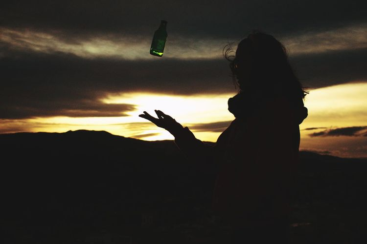 Silhouette woman holding smart phone against sky during sunset