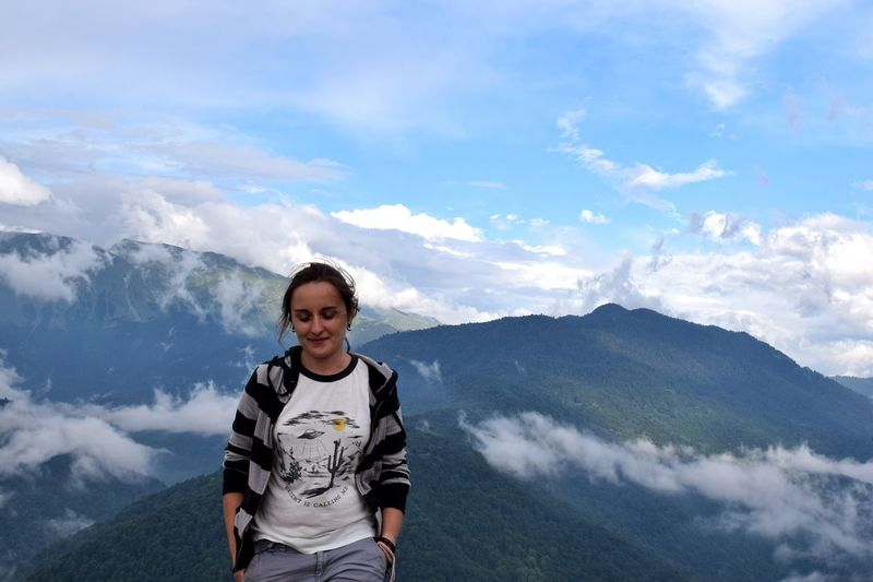 Smiling young woman standing on mountain against sky