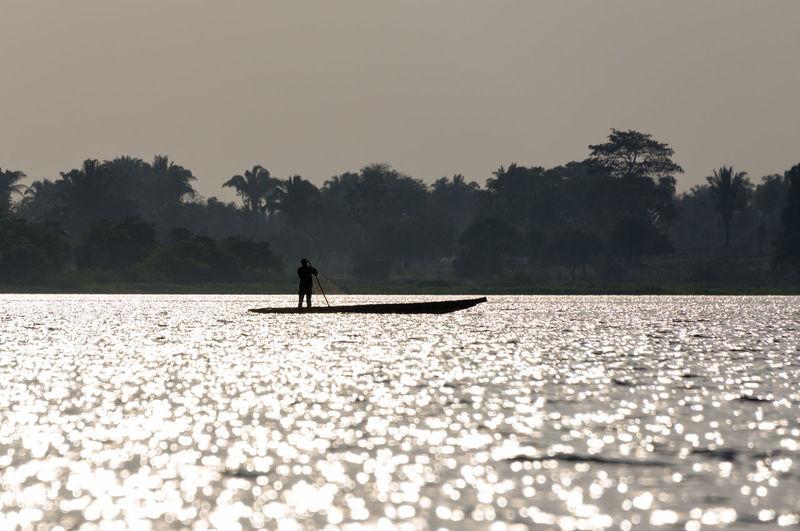 Silhouette fisherman sailing canoe in magdalena river