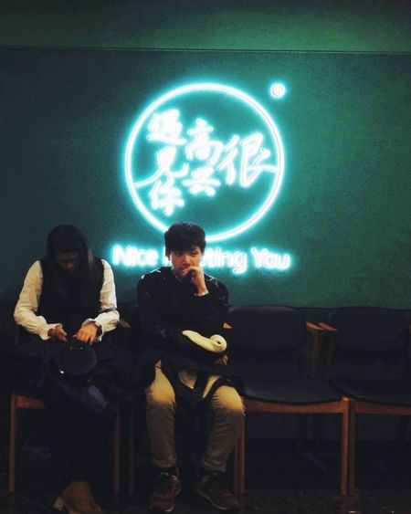 Text Beijing China Sitting Illuminated Front View Full Length Real People Lifestyles Young Adult Leisure Activity Two People Men Indoors  Young Women People Nice To Meet You Light And Reflection
