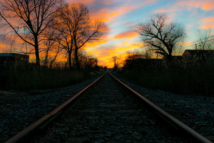 Diminishing perspective of railroad track against sky during sunset