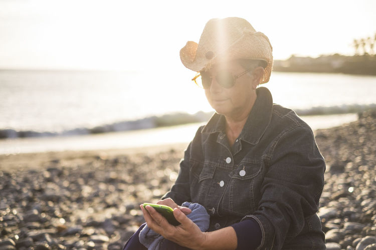 Senior woman using mobile phone while sitting at beach during sunset