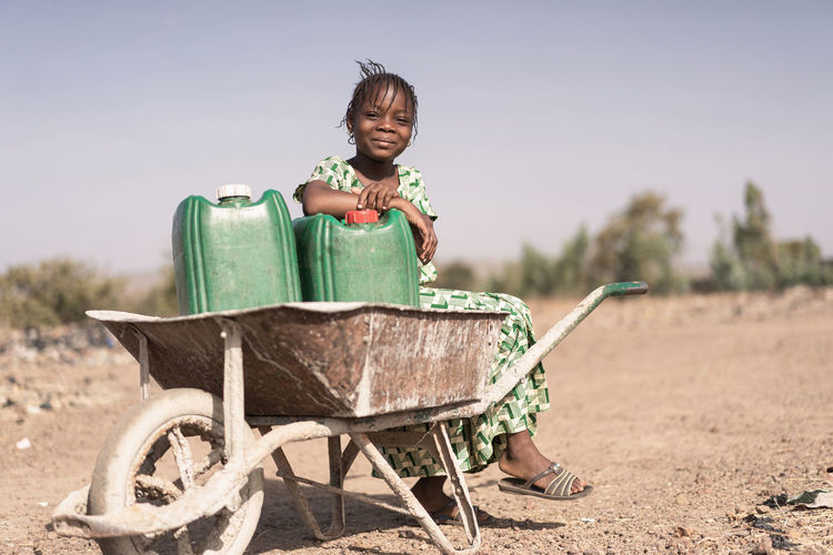 Full length portrait of girl sitting on wheelbarrow at land