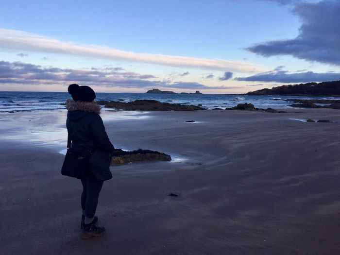 Keeping warm and looking out to sea. Fur Hood Bobble Hat  Woolly Hat Walking Boots Wet Sand Island Woman Shore Sea Beach Cloud - Sky Water One Person Full Length Only Women One Woman Only Rear View Adult Sand Sky Beauty In Nature Walking Travel Destinations Scenics
