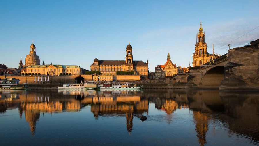 Boats Moored On River By Dresden Frauenkirche During Sunset