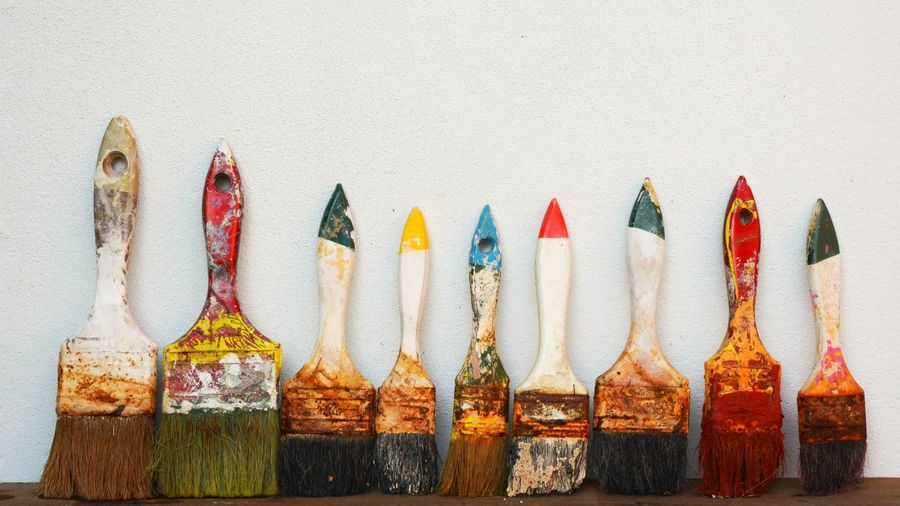 Close-up of paintbrushes against white wall