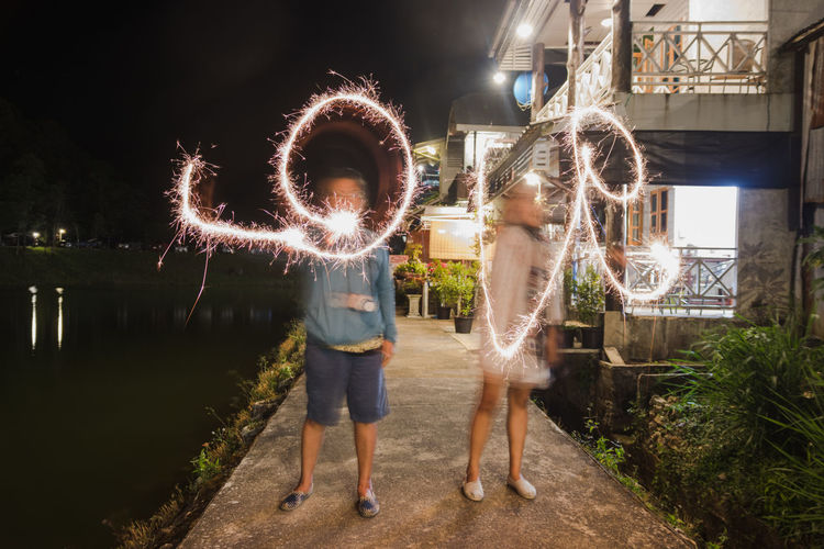 Architecture Night People Motion Real People Men Women Rear View Glowing Outdoors Firework Illuminated Long Exposure Sparkler Adult Lifestyles Full Length Two People Blurred Motion Casual Clothing Leisure Activity Valentine's Day  Love