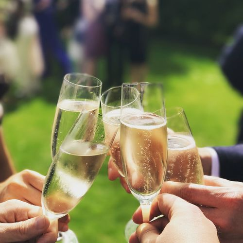Cropped hands toasting champagne flutes