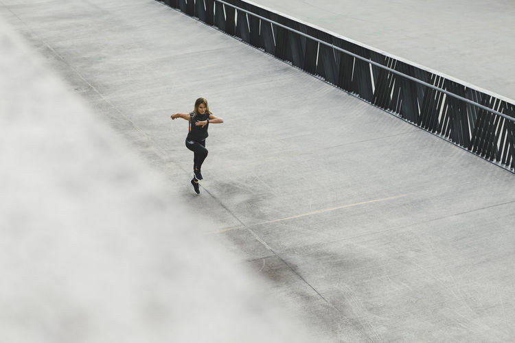 Woman running outdoors in the city, top view of fitness girl running Jogging Time Running Adult Architecture Built Structure Concrete Day Direction Effort Full Length High Angle View Jogging Leisure Activity Lifestyles Nature One Person Outdoors Railing Sport Sports Clothing Standing The Way Forward Urban Women Young Adult