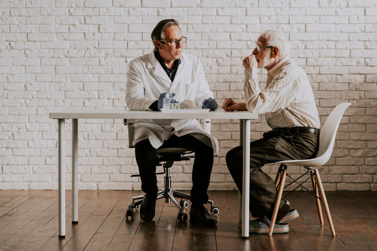 Men sitting on table against wall