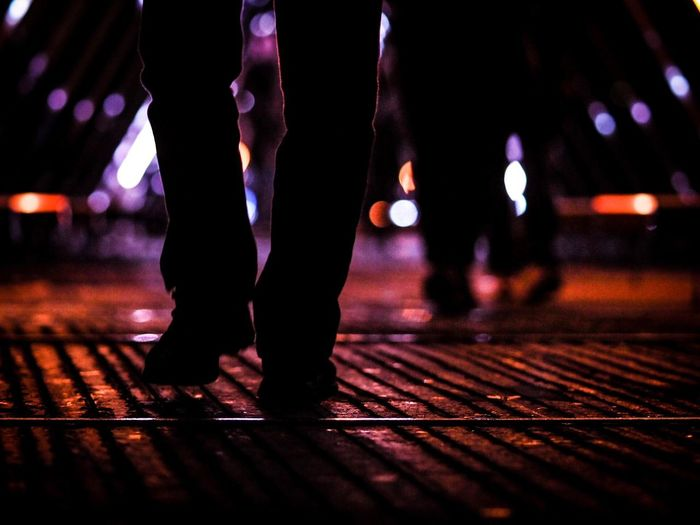 Low section of people walking on illuminated street