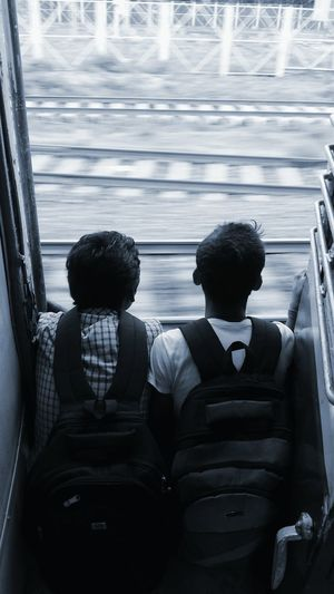 Teenage boys with bags sitting at door of train