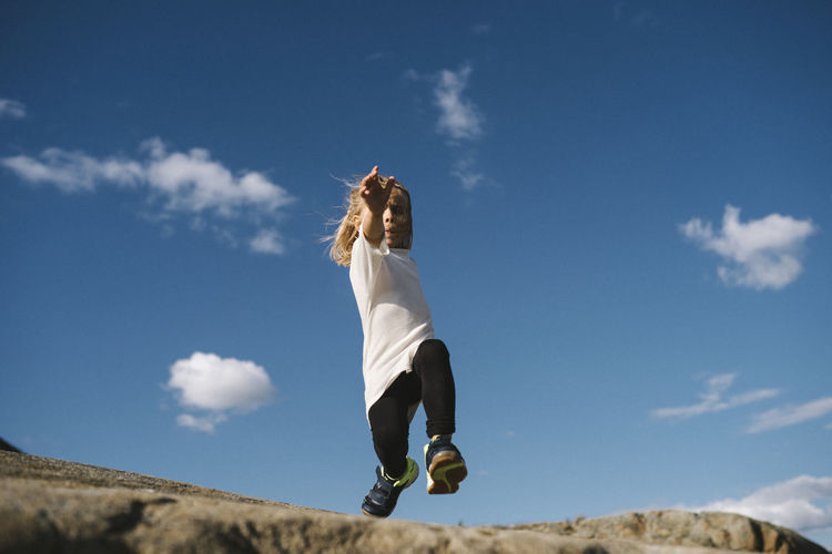 Low angle view of woman jumping against sky