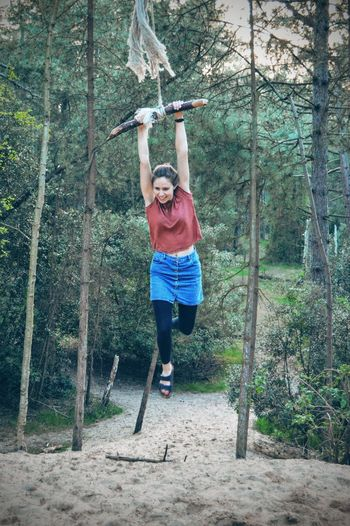 Full length of playful young woman on rope swing in forest