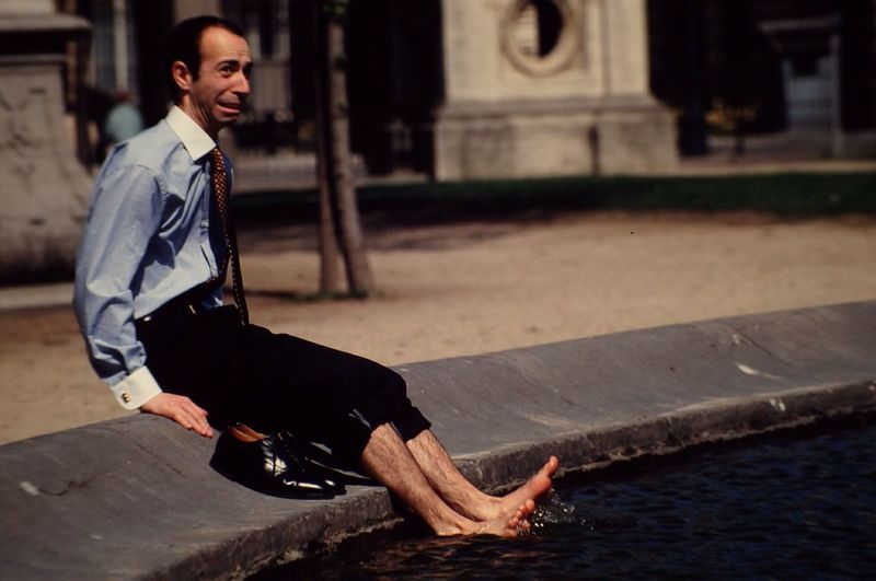 Businessman Sitting By Pond In City