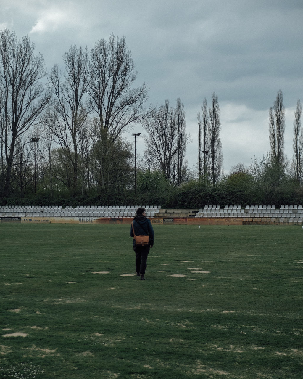 FULL LENGTH REAR VIEW OF MAN STANDING ON FIELD