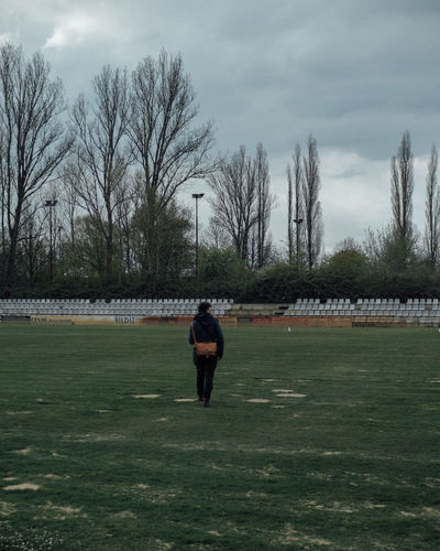 Rear view of man standing on field against sky