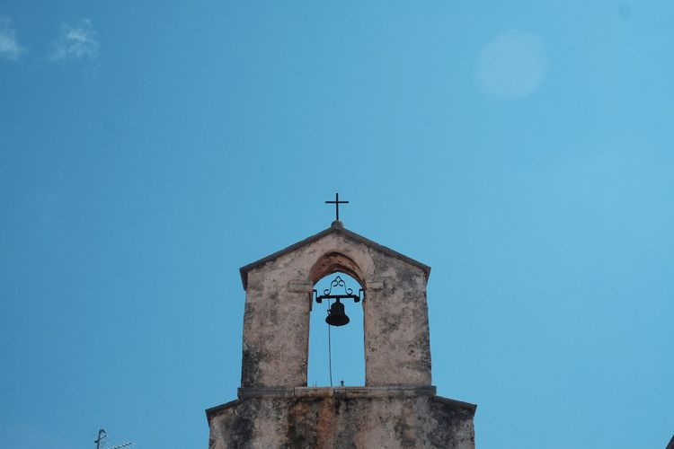 Low angle view of rustic church against clear blue sky